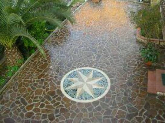 Crazy Paving in  slabs of porphyry  with compass rose.