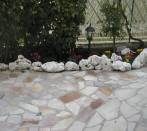 Flowerbed witk tumbled rocks in limestone