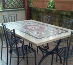 Table with iron chairs with mosaic under a veranda